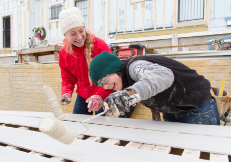 DC Habitat volunteers paint siding for a new home in SE DC.