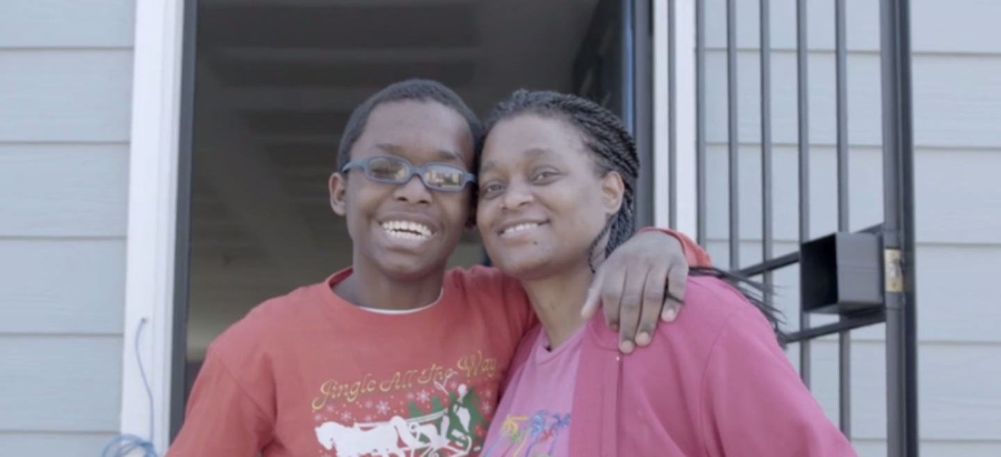 DC Habitat homeowner Andrea and her son smile in front of their home.