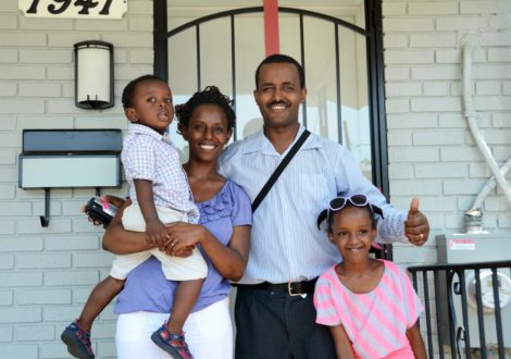 A DC Habitat family smiles on front of their home.