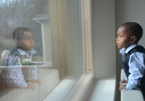 The child of a DC Habitat homeowner looks out of the window of his new home.