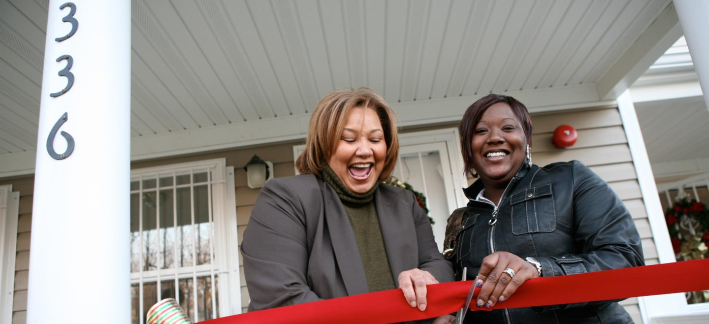 A DC Habitat homeowner excitedly cuts the ribbon on her new home.
