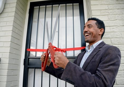 DC Habitat Homeowner Michael smiles as he cuts the ribbon on his new home.