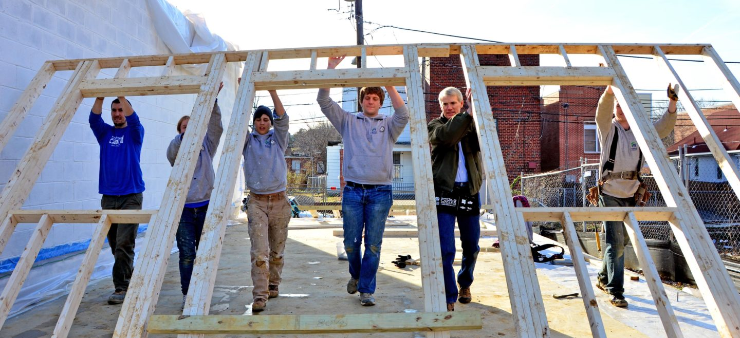DC Habitat AmeriCorps members help raise a wall with Senator Rob Portman.