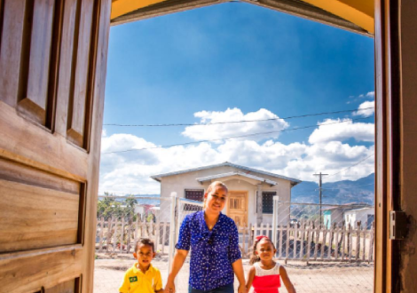 A Habitat family walks through the doorway of their home.