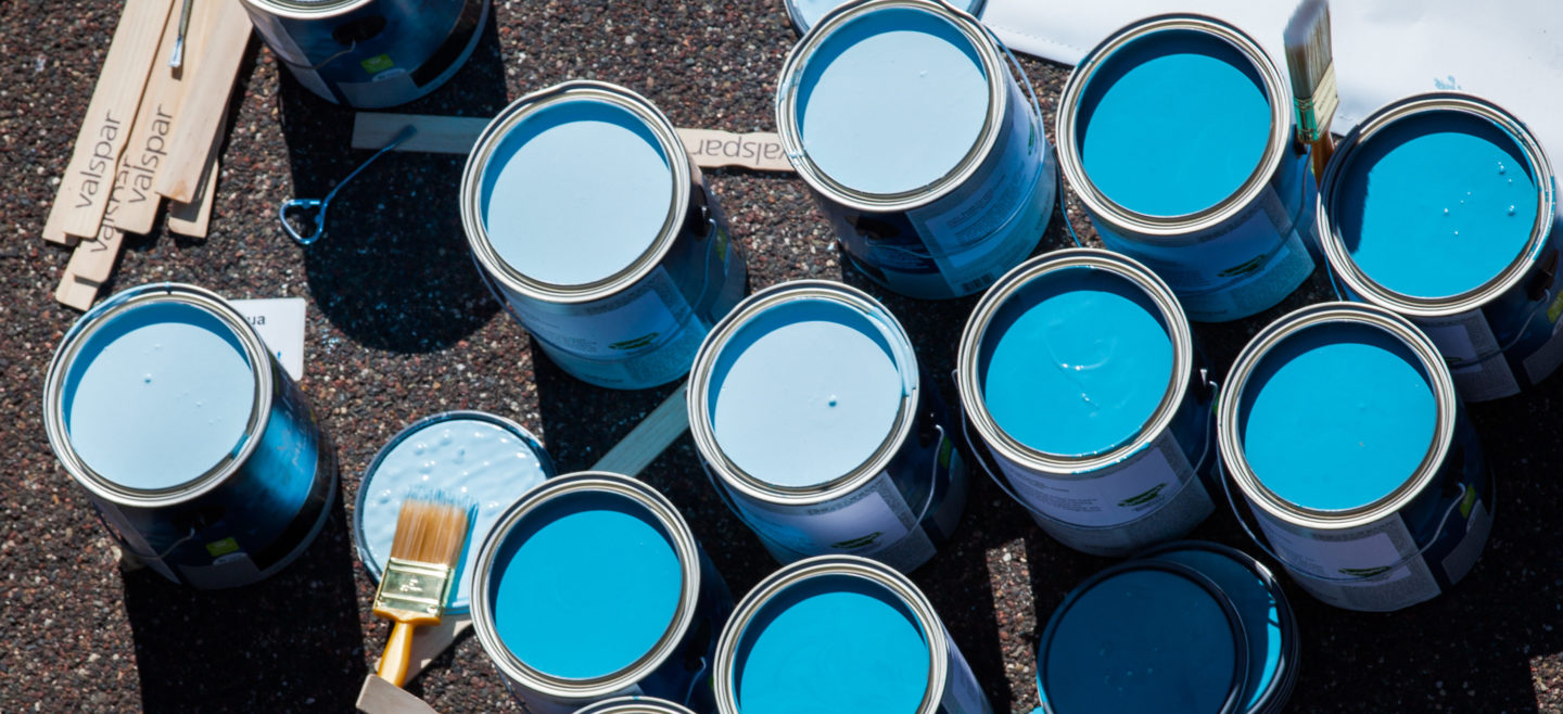 Open cans of blue paint sit in the driveway of a Habitat home on painting day.