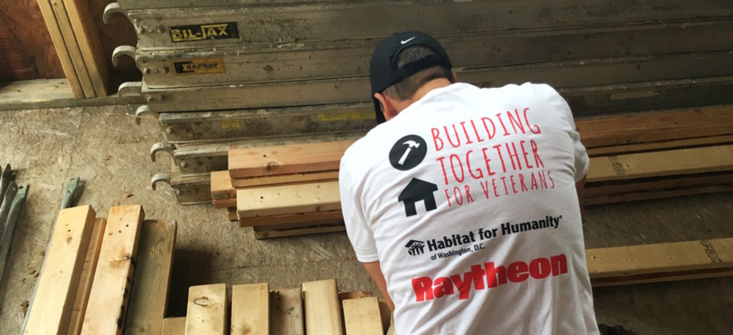 A Raytheon volunteer helps frame a DC Habitat home.