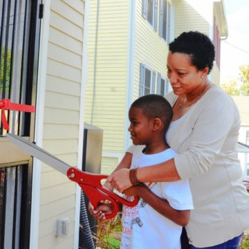 DC Habitat Homeowner Rodneyca and her son cut the ribbon on their new home.